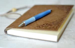 Leather bound journal and blue pen on marble background